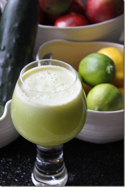 Green Juice Drink made with Cucumbers, Apples, and Celery. Lemon and Lime in the background